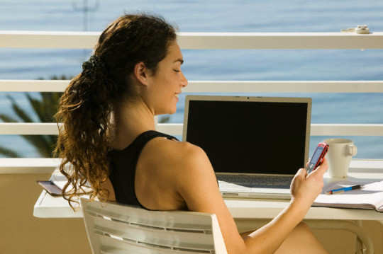 Woman on Balcony With Cell Phone and Laptop