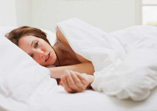 woman-laying-in-bed-with-blanket