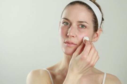 woman-wipes-face-with-cotton-ball