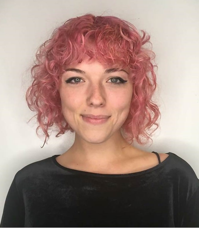 short pastel pink curly hair with bangs